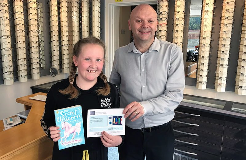 Jennifer collecting her book token from Anthony McIvor at Keyes Eyecare in Newcastle upon Tyne