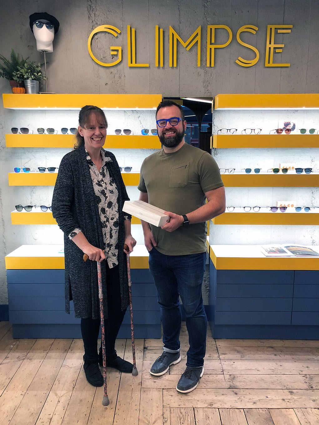 Joanne Griffiths collecting her iPad from Matthew Rose at Glimpse Opticians in Birmingham