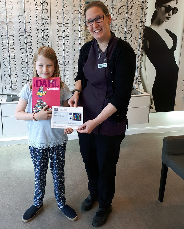 Matilda collecting her book token from Jess Pilcher at Classic Eyes opticians in Bournemouth
