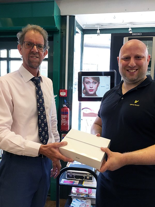 Ryan Calvert collecting his iPad from Carl Farrington at Welbourne Opticians in Lancaster