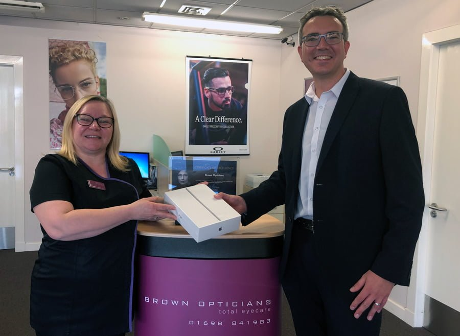 Eoin Chisholm (Seiko Business Development Manager) presenting the iPad to Jen at Brown Opticians in Cardonald for collection by  Joanne Barlow