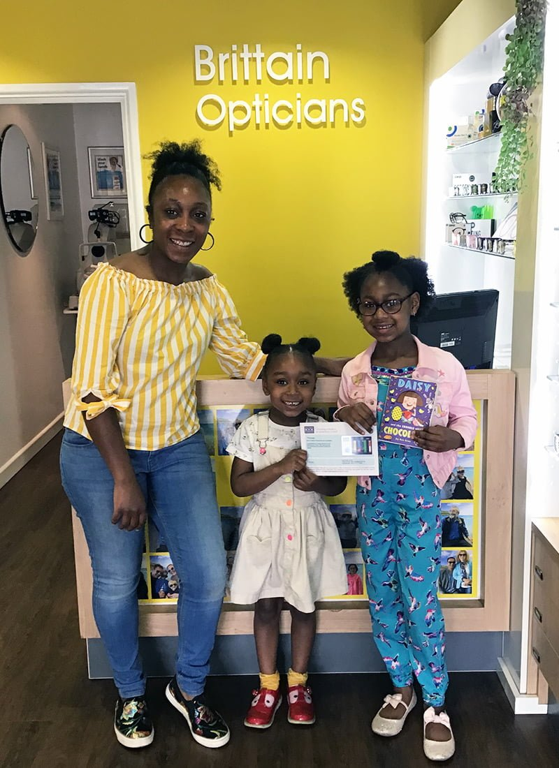 Xia collecting her book token from Brittain Opticians in Harborne, Birmingham